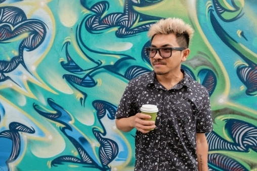 Asian man holding a latte standing in front of a green and blue picture